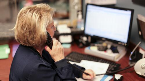 Staff member answering a call on her desk phone.